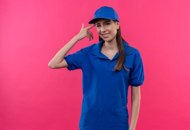 Młoda dziewczyna dostawy w niebieskim mundurze i czapce wygląda na zdezorientowaną, wskazując jej świątynię za błąd