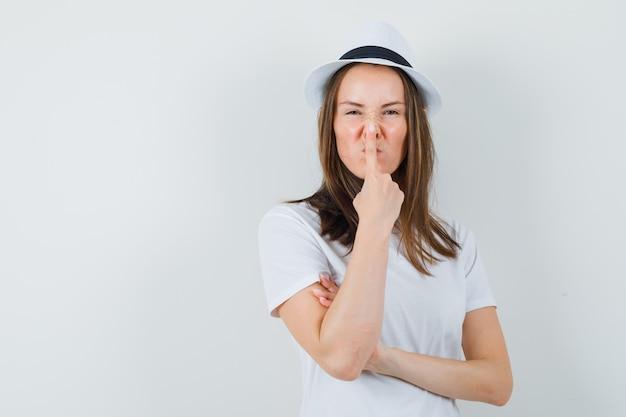 Młoda dziewczyna dotyka nosa palcem w biały t-shirt kapelusz