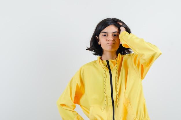 Młoda dziewczyna drapie głowę i trzyma jedną rękę na talii w żółtej bomberce i wygląda poważnie