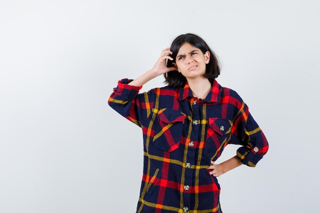 Młoda dziewczyna drapie się po głowie trzymając rękę w pasie w kraciastej koszuli i wygląda na zmęczoną. przedni widok.