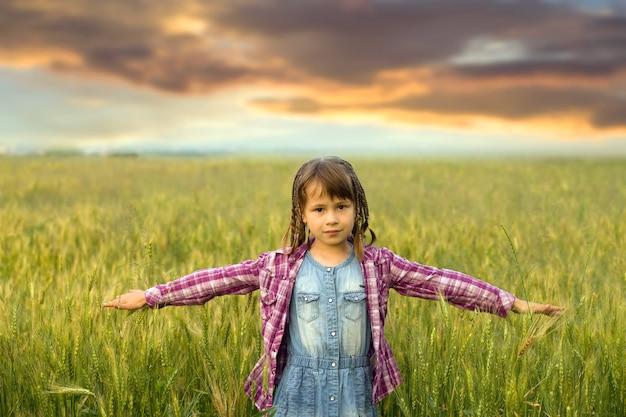Młoda dziewczyna dziecko z rozpostartymi ramionami stojąc samotnie na zewnątrz w polu pszenicy pod zachmurzonym niebem na mglistym wiejskim zachodzie słońca w tle.