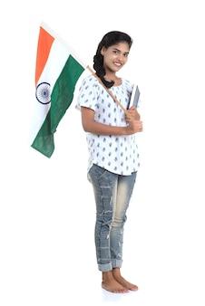 Młoda dziewczyna dzień niepodległości indii lub dzień republiki indii z flagą indii lub tricolor i książki na białym tle