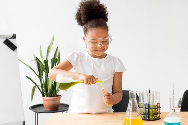 Młoda dziewczyna eksperymentuje z miksturami dla chemii