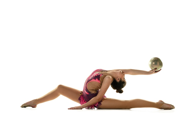 Młoda dziewczyna elastyczne na białym tle na tle białego studia. nastoletnia modelka jako artysta gimnastyki artystycznej ćwiczy ze sprzętem. ćwiczenia na elastyczność, równowagę. łaska w ruchu, sport.
