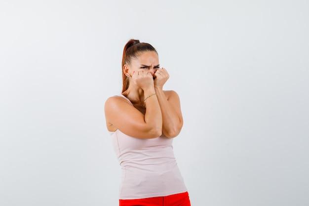 Młoda dziewczyna emocjonalnie gryzie pięści w beżowym topie i czerwonych spodniach i wygląda na zaniepokojoną. przedni widok.
