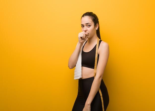 Młoda dziewczyna fitness kaszel, chora z powodu wirusa lub infekcji