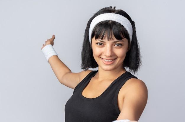 Młoda dziewczyna fitness nosi opaskę patrząc na kamerę z uśmiechem na szczęśliwej twarzy stojącej na białym tle