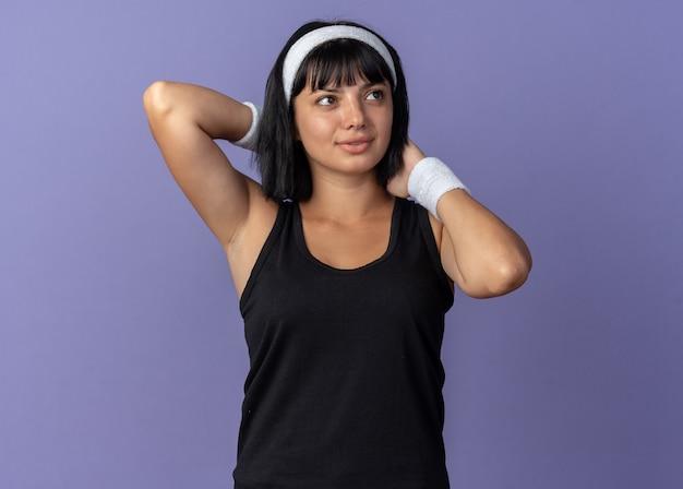 Młoda dziewczyna fitness nosi opaskę, rozciągając ręce, patrząc pewnie, stojąc na niebiesko