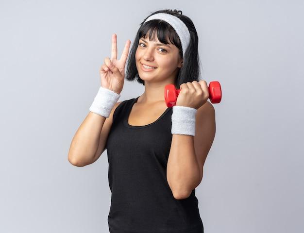 Młoda dziewczyna fitness nosi opaskę, trzymając hantle, robi ćwiczenia, patrząc na kamerę, uśmiechając się pokazując znak v stojący na białym tle