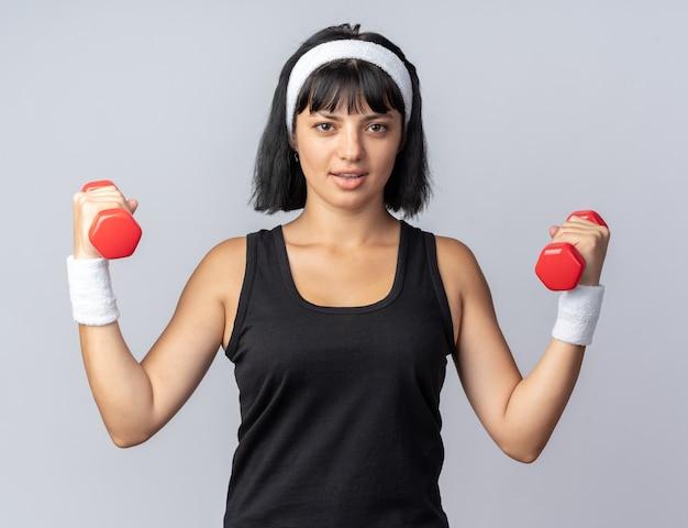 Młoda dziewczyna fitness nosi opaskę, trzymając hantle, robi ćwiczenia, patrząc pewnie, stojąc na białym tle