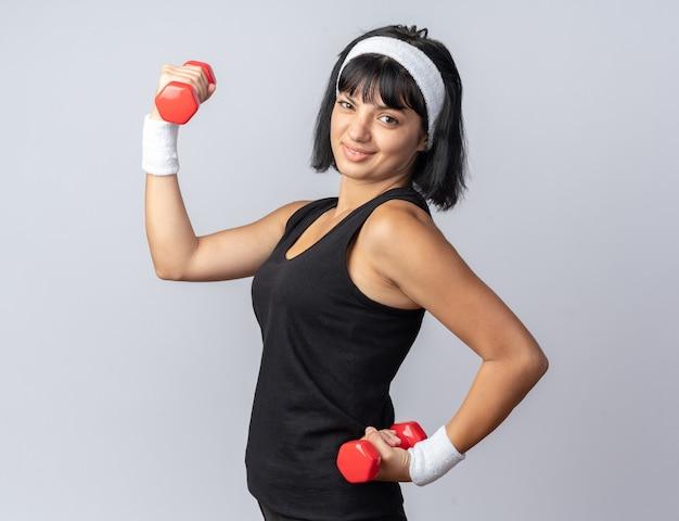 Młoda dziewczyna fitness nosi opaskę, trzymając hantle, robi ćwiczenia, patrząc pewnie, stojąc na białym