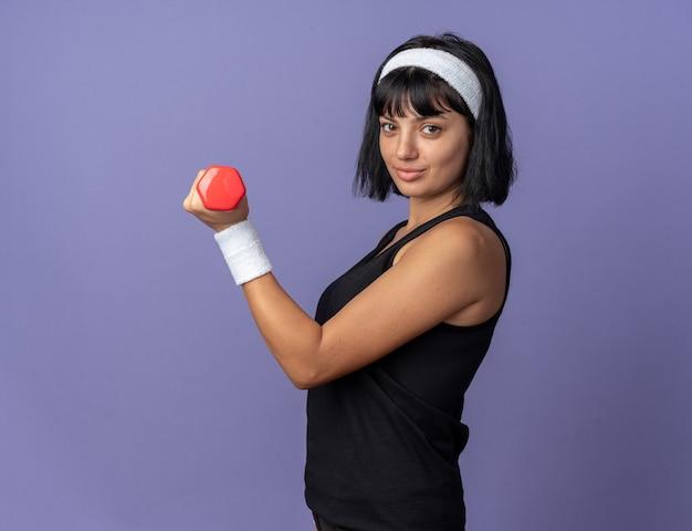 Młoda dziewczyna fitness nosi opaskę, trzymając hantle, robi ćwiczenia, patrząc pewnie uśmiechając się, stojąc na niebieskim tle