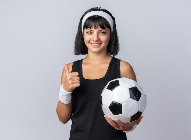 Młoda dziewczyna fitness nosi opaskę, trzymając piłkę nożną, patrząc na kamerę, uśmiechając się, kciuki do góry, stojąc nad białymi