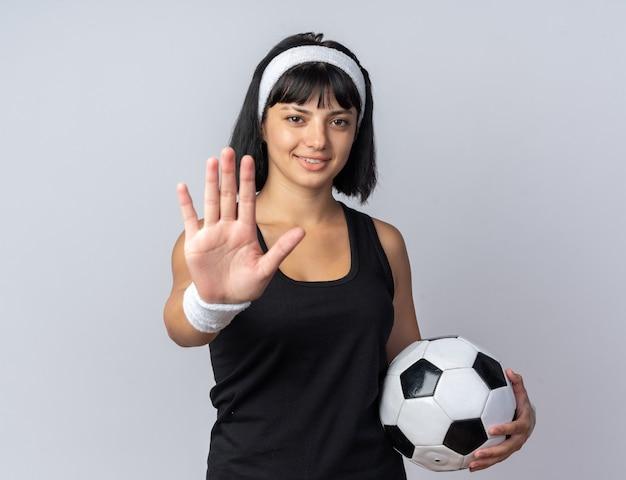 Młoda dziewczyna fitness nosi opaskę, trzymając piłkę nożną, patrząc na kamery, uśmiechając się, robiąc gest zatrzymania ręką stojącą nad białym