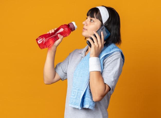Młoda dziewczyna fitness nosi opaskę z ręcznikiem na ramieniu, trzymając butelkę wody, wyglądając pewnie podczas rozmowy przez telefon komórkowy