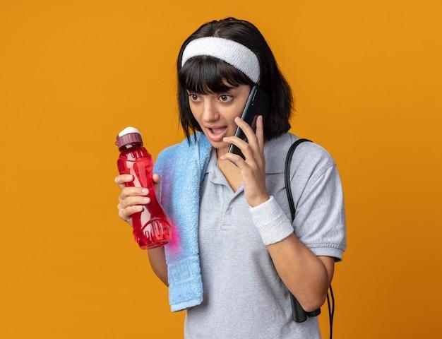 Młoda dziewczyna fitness nosi opaskę z ręcznikiem na ramieniu, trzymając butelkę wody