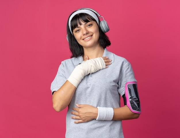 Młoda dziewczyna fitness nosi opaskę ze słuchawkami i opaską na smartfona, patrząc na kamerę, uśmiechając się pewnie stojąc na różowym tle