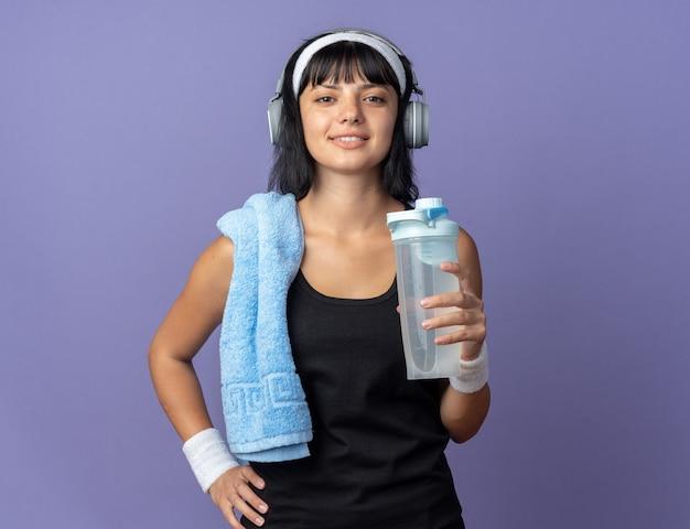 Młoda dziewczyna fitness nosi opaskę ze słuchawkami i ręcznikiem wokół szyi, trzymając butelkę wody, patrząc na kamery, uśmiechając się pewnie