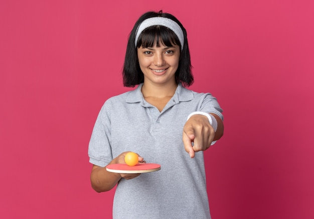 Młoda dziewczyna fitness nosi pałąk, trzymając rakietę i piłkę do tenisa stołowego, wskazując palcem wskazującym na aparat, uśmiechając się z szczęśliwą twarzą stojącą na różowym tle
