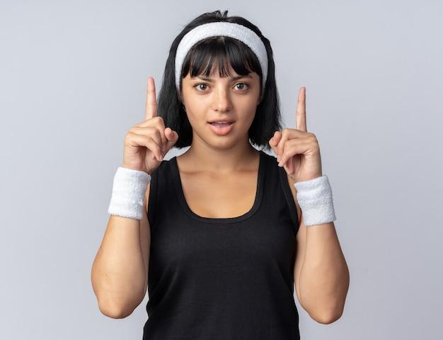 Młoda dziewczyna fitness nosząca opaskę patrząc na kamerę szczęśliwa i zdziwiona pokazująca palce wskazujące stojące nad białymi