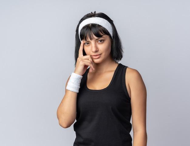 Młoda dziewczyna fitness nosząca opaskę, patrząca na kamerę z uśmiechem na inteligentnej twarzy, wskazująca palcem wskazującym na jej świątynię stojącą na białym tle