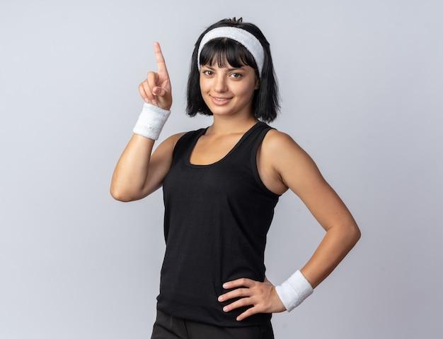 Młoda dziewczyna fitness nosząca opaskę, patrząca w kamerę, uśmiechnięta pewnie, wskazując palcem wskazującym w górę, stojąc nad białymi