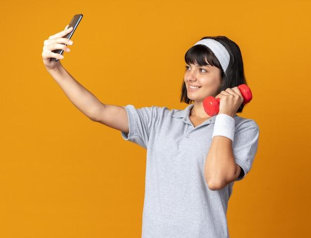 Młoda dziewczyna fitness nosząca opaskę, trzymająca hantle, robi selfie za pomocą smartfona, uśmiechając się radośnie, stojąc nad pomarańczą