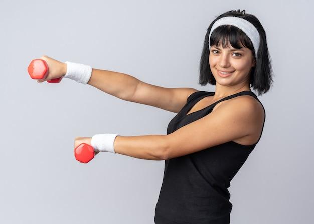 Młoda dziewczyna fitness nosząca opaskę, trzymająca hantle, wykonująca ćwiczenia, wyglądająca pewnie uśmiechnięta, stojąca nad białymi