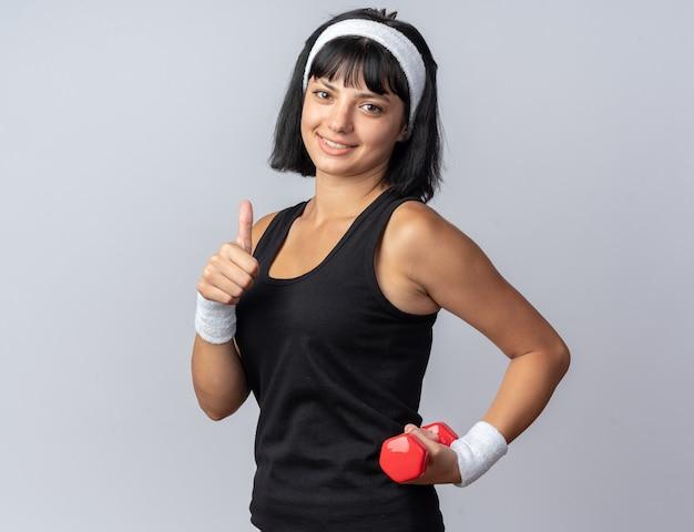Młoda dziewczyna fitness nosząca opaskę, trzymająca hantle, wykonująca ćwiczenia, wyglądająca pewnie uśmiechnięta