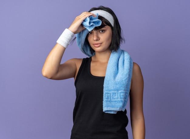 Młoda dziewczyna fitness nosząca opaskę z ręcznikiem na ramieniu, ocierając czoło, wyglądając na zmęczoną, stojąc na niebieskim tle