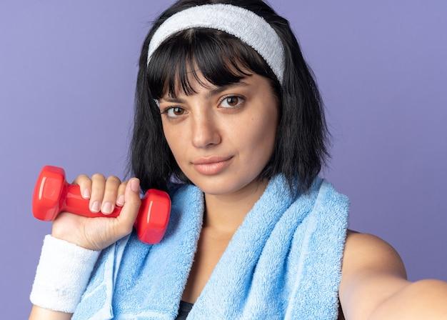 Młoda dziewczyna fitness nosząca opaskę z ręcznikiem na szyi trzymająca hantle patrząca na kamerę z pewnym siebie wyrazem stojącym na niebieskim tle
