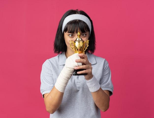 Młoda dziewczyna fitness nosząca opaskę z zabandażowaną ręką trzymająca trofeum, patrząc na to z zaskoczeniem i radością