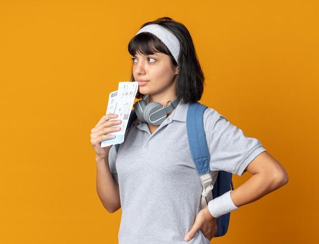 Młoda dziewczyna fitness nosząca opaskę ze słuchawkami na szyi, trzymająca bilety lotnicze, patrząc na bok, zdziwiona, stojąc na pomarańczowym tle