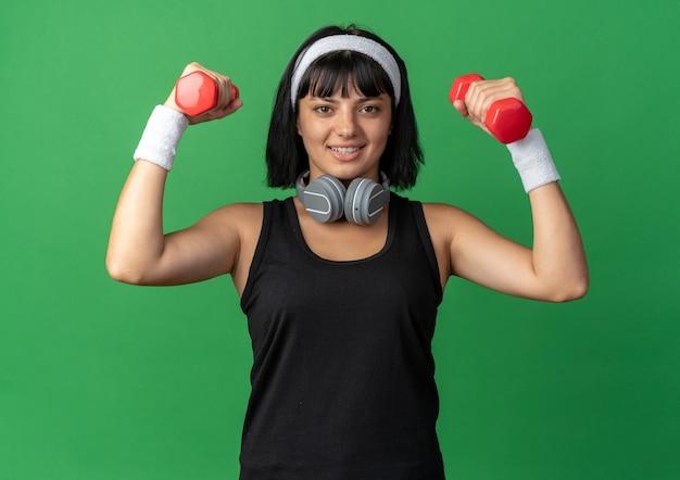 Młoda dziewczyna fitness nosząca opaskę ze słuchawkami, trzymająca hantle, wykonująca ćwiczenia, wyglądająca pewnie uśmiechnięta
