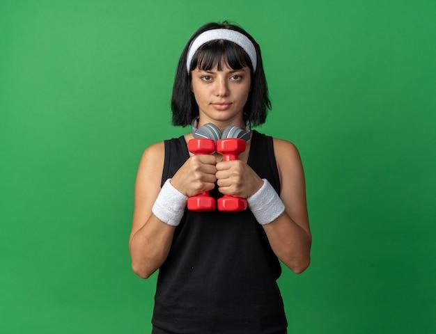 Młoda dziewczyna fitness nosząca opaskę ze słuchawkami, trzymająca hantle, wykonująca ćwiczenia, wyglądająca pewnie