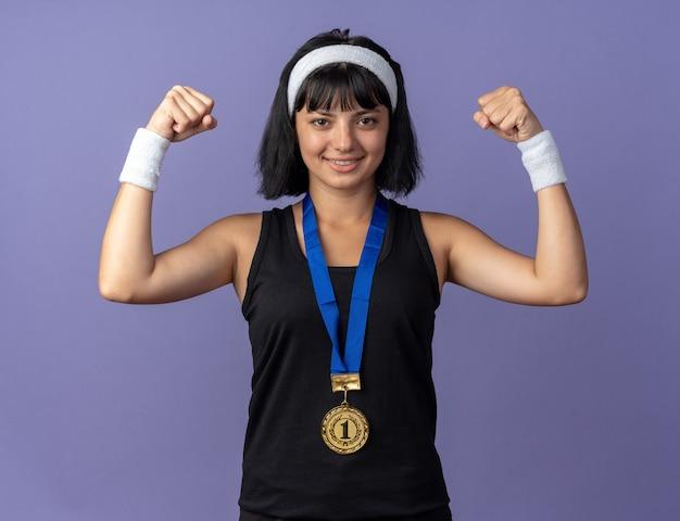 Młoda dziewczyna fitness nosząca opaskę ze złotym medalem wokół szyi, unosząca pięści szczęśliwa i pewna siebie, pozująca jak zwycięzca stojący na niebieskim tle
