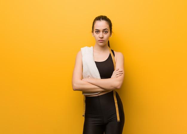 Młoda dziewczyna fitness przekraczania broni zrelaksowany
