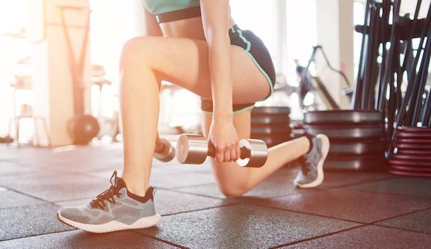 Młoda Dziewczyna Fitness Robi Rzuty Na Nogi Z Hantlami W Rękach Na Siłowni. Premium Zdjęcia