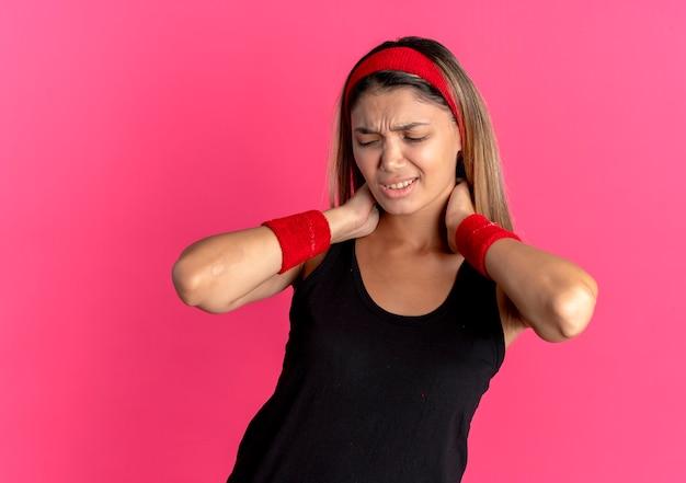 Młoda dziewczyna fitness w czarnej odzieży sportowej i czerwonej opasce dotyka jej szyi, patrząc na zły ból na różowo