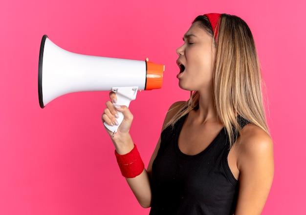 Młoda dziewczyna fitness w czarnej odzieży sportowej i czerwonej opasce krzyczy do megafonu na różowo