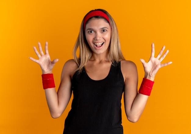 Młoda dziewczyna fitness w czarnej odzieży sportowej i czerwonej opasce, podnosząc ręce w kapitulacji, uśmiechając się radośnie stojąc nad pomarańczową ścianą