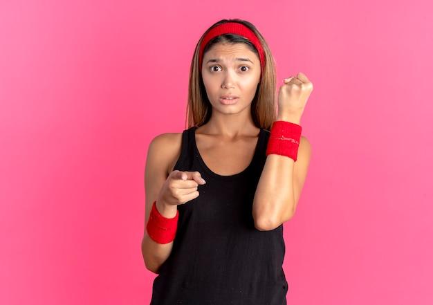 Młoda dziewczyna fitness w czarnej odzieży sportowej i czerwonej opasce szuka zdezorientowanego zaciśniętej pięści wskazującej palcem na aparat na różowo