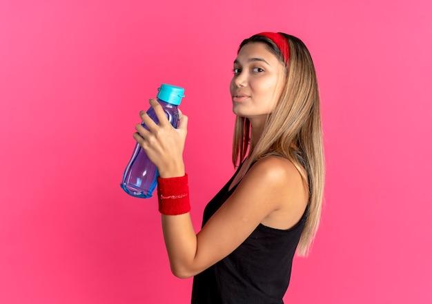 Młoda dziewczyna fitness w czarnej odzieży sportowej i czerwonej opasce trzyma butelkę wody, uśmiechając się pewnie na różowo