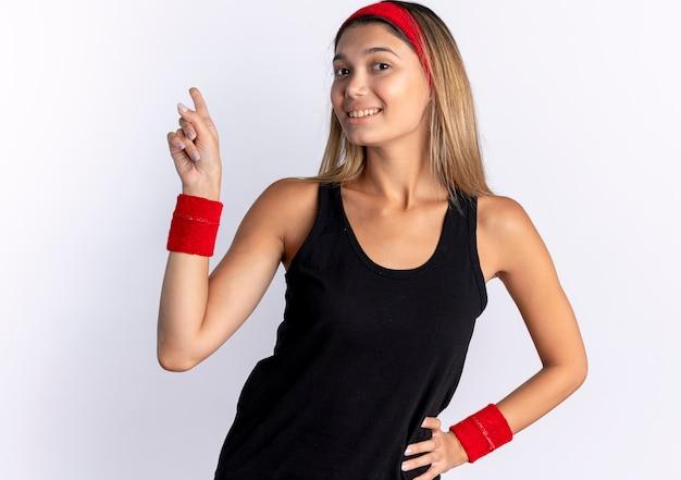 Młoda dziewczyna fitness w czarnej odzieży sportowej i czerwonej opasce uśmiecha się pewnie, wskazując palcem wskazującym na białej ścianie