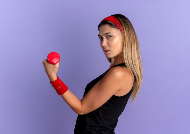 Młoda dziewczyna fitness w czarnej odzieży sportowej i czerwonej opasce z hantlami pokazuje bicepsy patrząc pewnie na niebiesko