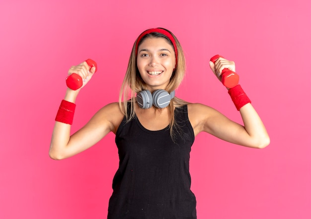 Młoda dziewczyna fitness w czarnej odzieży sportowej i czerwonej opasce z hantlami, uśmiechając się radośnie stojąc na różowej ścianie