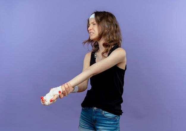 Młoda dziewczyna fitness w czarnej odzieży sportowej z opaską dotykającą jej zabandażowanego nadgarstka czuje ból stojąc na niebieskiej ścianie