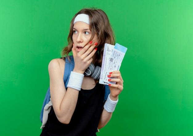 Młoda dziewczyna fitness w czarnej odzieży sportowej z opaską i plecakiem, trzymając bilety lotnicze, patrząc na bok zdumiony i zaskoczony, stojąc nad zieloną ścianą