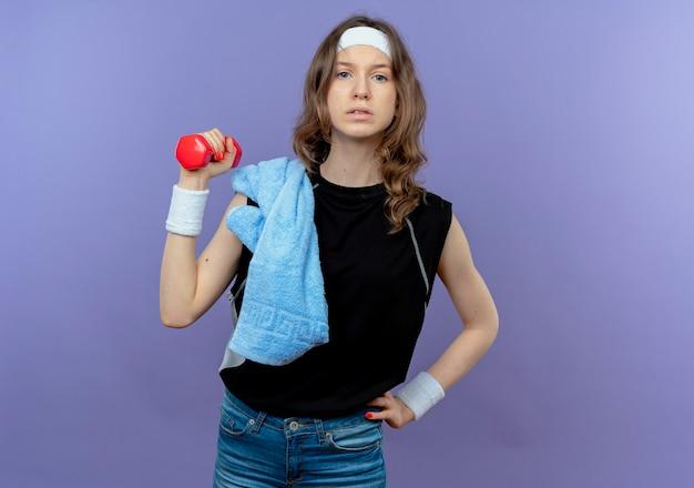 Młoda dziewczyna fitness w czarnej odzieży sportowej z opaską i ręcznikiem na ramieniu, trzymając hantle, robi ćwiczenia patrząc pewnie na niebiesko