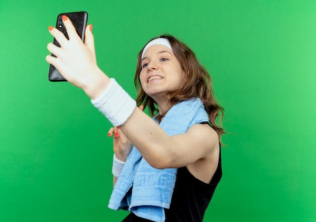 Młoda dziewczyna fitness w czarnej odzieży sportowej z opaską i ręcznikiem na szyi, biorąc selfie przy użyciu swojego smartfona stojącego na zielonej ścianie
